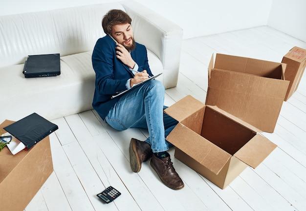 Zakenman in de buurt van dozen met dingen uitpakken verhuizen naar een nieuwe officiële levensstijl van het kantoor van de locatie