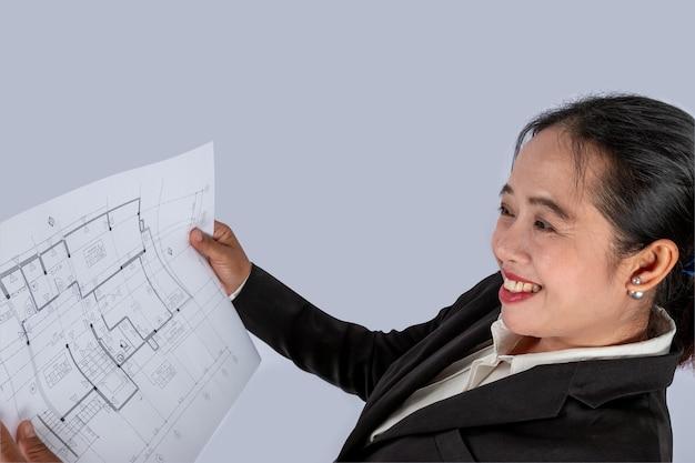 Zakenman in de hand heeft een bouwplan of architectonisch plan, gebruikt voor gerelateerde professionele huizenhandel, onroerend goed, constructie.