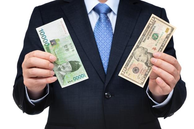 Zakenman in de hand houden van amerikaanse dollars en koreaanse valuta.