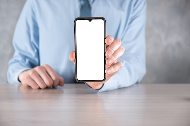 Zakenman in een blauw shirt op werkplek aan tafel met een mobiele telefoon, smartphone met een wit scherm.