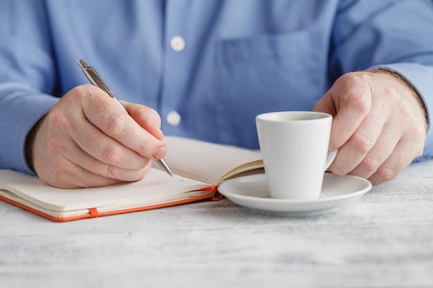Zakenman in een blauwe jas met een kopje koffie