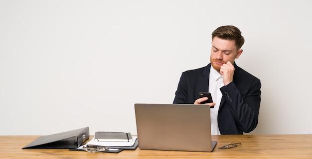 Zakenman in een bureau dat en een bericht denkt verzendt