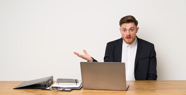 Zakenman in een bureau dat twijfelsgebaar maakt