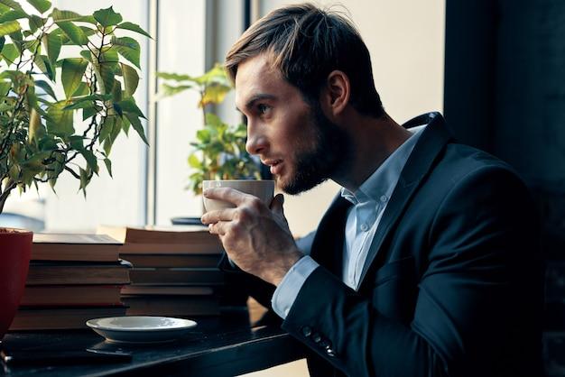 Zakenman in een cafékostuum die een café-ontbijt drinkt drinking