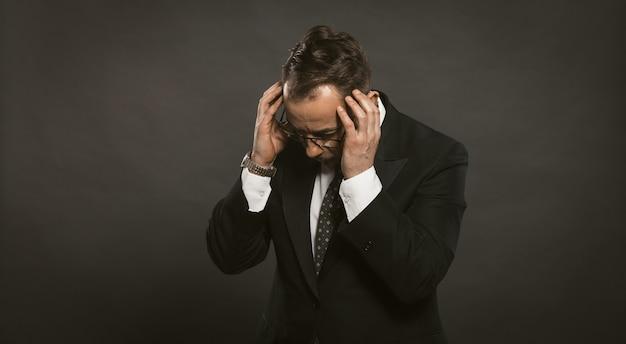 Zakenman in een depressie houdt zijn handen op zijn hoofd. man in pak op zwarte muur klemde zijn hoofd in paniek met zijn handen. probleem bedrijfsconcept