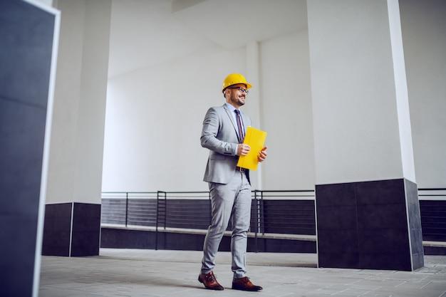Zakenman in een grijs pak met een gele beschermende helm op zijn hoofd buiten lopen en gele bestand in zijn handen houden