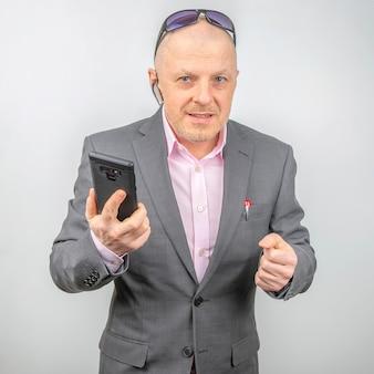 Zakenman in een jasje met een mobiele telefoon in zijn hand op een lichte achtergrond