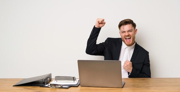 Zakenman in een kantoor dat een overwinning viert