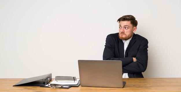Zakenman in een kantoor dat twijfels gebaar maakt terwijl het opheffen van de schouders