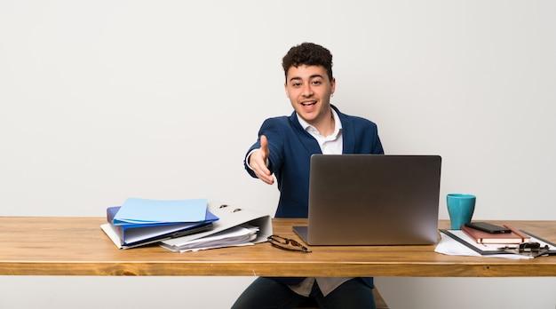 Zakenman in een kantoor handen schudden voor het sluiten van een goede deal