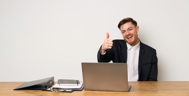 Zakenman in een kantoor met duimen omhoog omdat er iets goeds is gebeurd