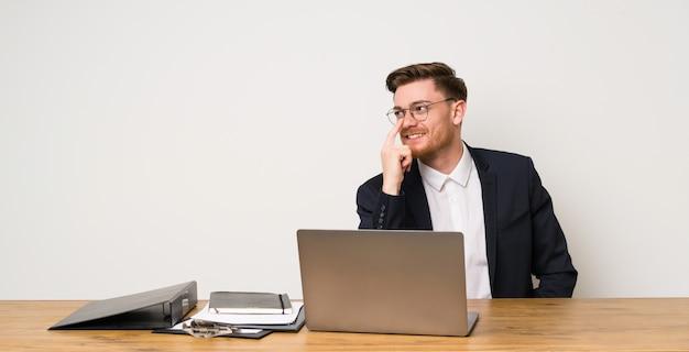 Zakenman in een kantoor met een bril en glimlachen