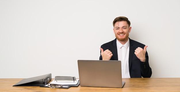 Zakenman in een kantoor met thumbs up gebaar en glimlachen