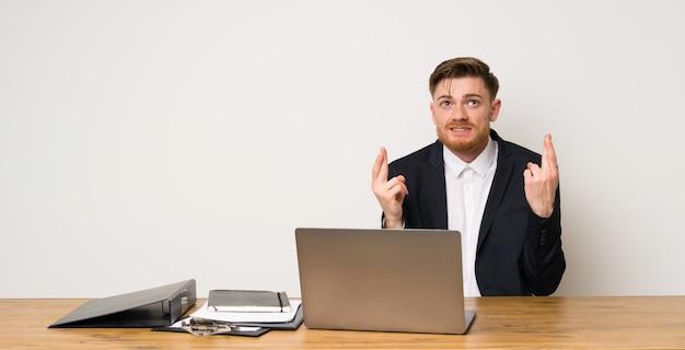 Zakenman in een kantoor met vingers kruising en het beste wensen