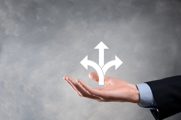 Zakenman in een pak heeft een bord met drie richtingen. bij twijfel, moeten kiezen tussen drie verschillende keuzes die worden aangegeven door pijlen die in tegengestelde richting wijzen. drie manieren om te kiezen