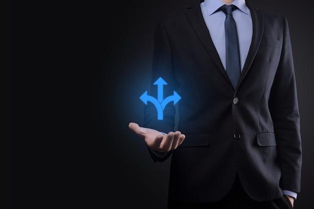 Zakenman in een pak houdt een bord vast met drie richtingen bij twijfel, die moet kiezen tussen drie verschillende keuzes, aangegeven door pijlen die in tegengestelde richting wijzen concept drie manieren om te kiezen
