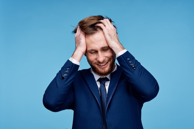 Zakenman in een pak houdt zijn hand op zijn hoofd financiële emotie