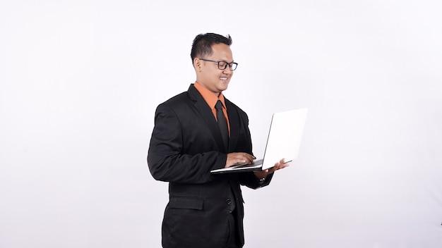 Zakenman in een pak met een laptopcomputer en kijken naar de camera geïsoleerd op een witte achtergrond