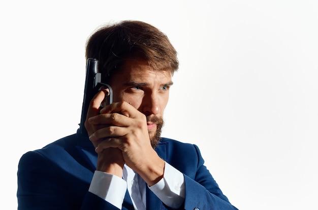 Zakenman in een pak met een pistool in zijn handen detective voorzichtigheidsmisdaad.