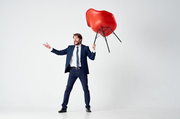Zakenman in een pak met een rode stoel in zijn handen boven zijn hoofdemoties