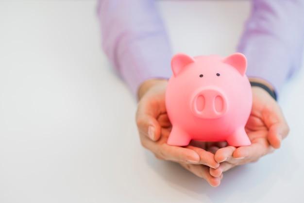 Zakenman in een pak met roze spaarvarken met beide handen, geïsoleerd op een witte achtergrond.