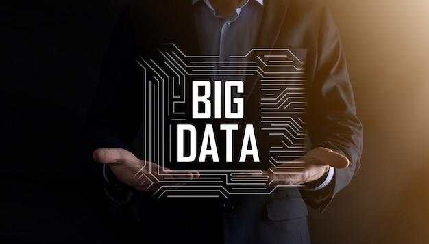 Zakenman in een pak op een donkere muur heeft het opschrift big data. opslag netwerk online server concept.social netwerk of business analytics vertegenwoordiging.