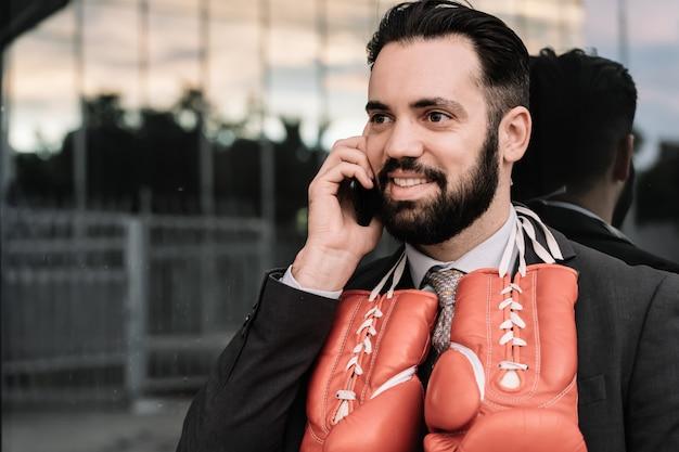Zakenman in een pak praten op zijn mobiele telefoon met rode bokshandschoenen opknoping van zijn nek leunend