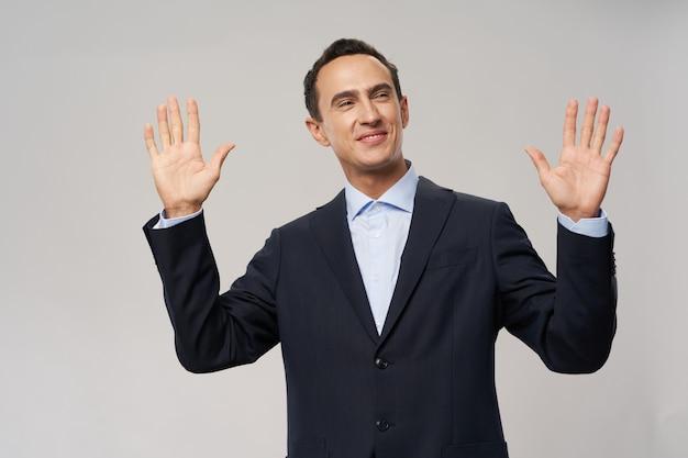 Zakenman in een pak stak zijn handen omhoog op een financieel model van een beige achtergrondjasje hoge kwaliteit foto