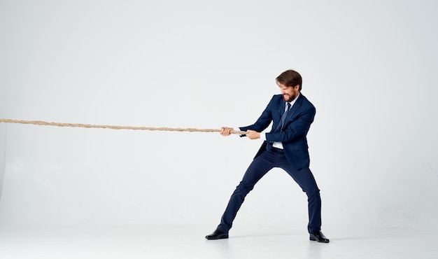 Zakenman in een pak trekt aan de lichte achtergrond van de touwstudio