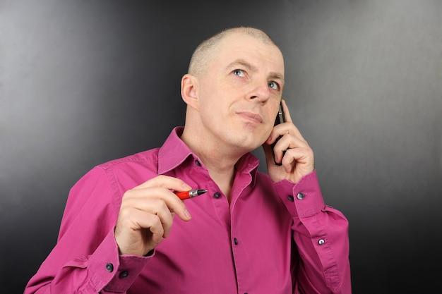 Zakenman in een roze shirt met een pen in de hand praten over een mobiele telefoon