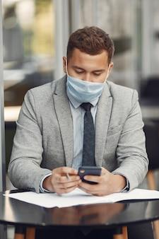 Zakenman in een stad. persoon in een masker. man met documenten en telefoon;