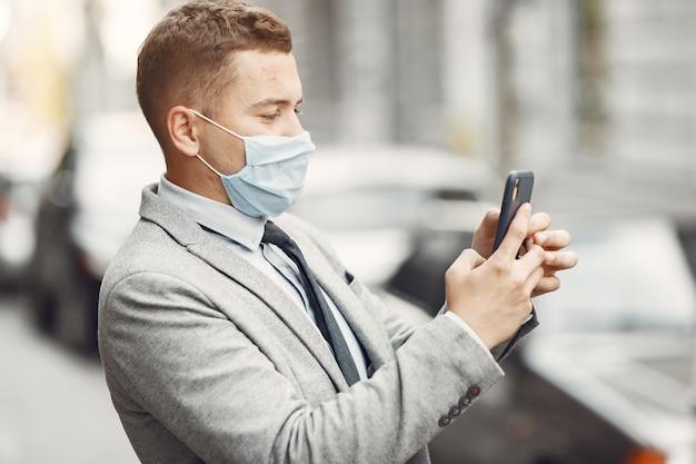 Zakenman in een stad. persoon in een masker. man met telefoon.
