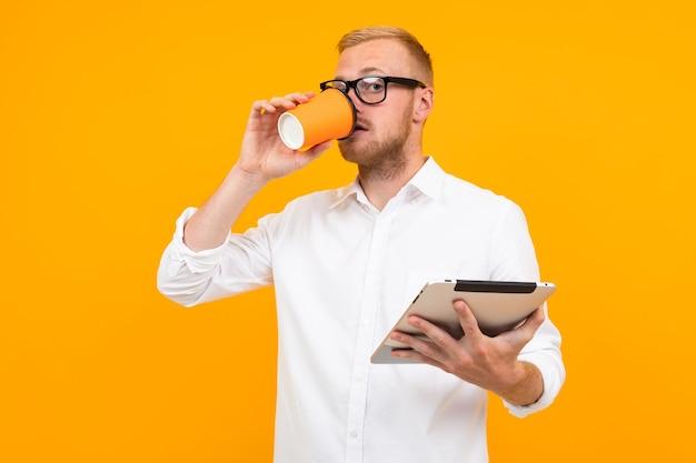 Zakenman in een wit overhemd met een tablet en een kopje koffie in de hand op een gele achtergrond met kopie ruimte.