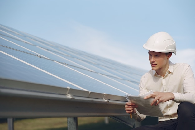 Zakenman in een witte helm in de buurt van zonne-batterij