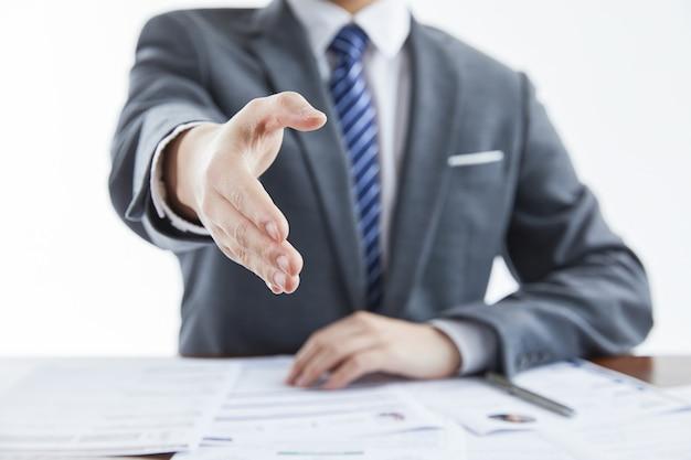 Zakenman in elegant pak op een zakelijke bijeenkomst die zijn hand geeft voor begroeting op kantoor