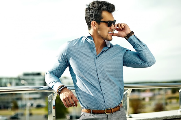 Zakenman in formele kleding en zonnebril met zijn telefoon