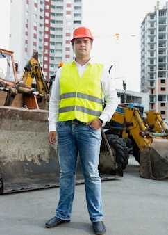 Zakenman in gele veiligheidsjas en veiligheidshelm poseren naast bulldozer
