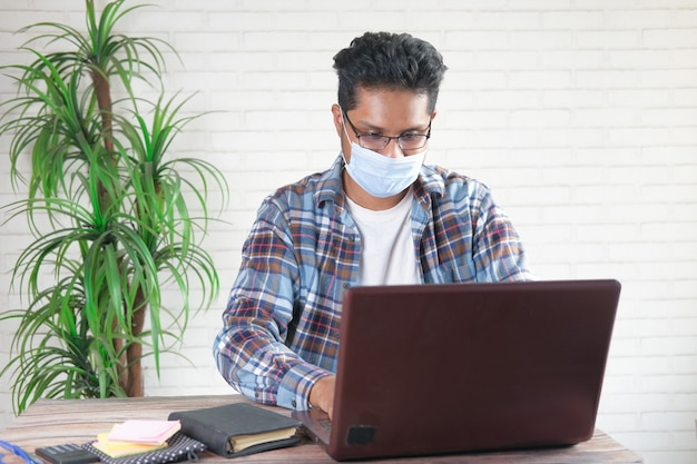 Zakenman in gezichtsmasker die aan laptop werkt