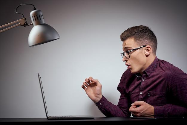 Zakenman in glazen en een shirt zit aan een tafel met opengeklapte laptop