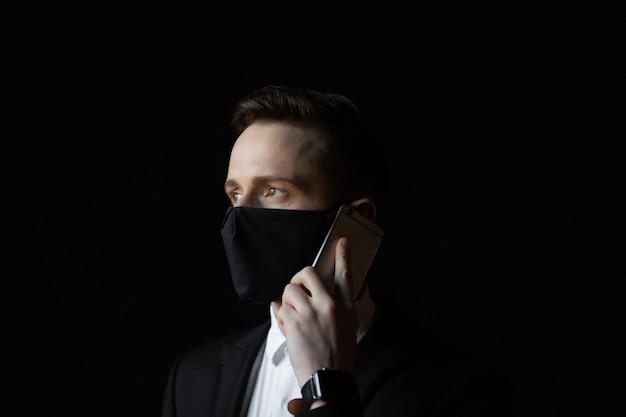 Zakenman in klassiek pak en beschermend masker spreekt aan de telefoon