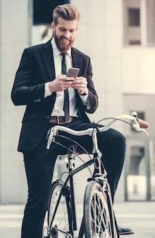 Zakenman in klassiek pak gebruikt een slimme telefoon.