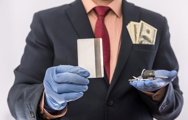 Zakenman in medische handschoenen met creditcard en autosleutel, met geld in poket, epidemische covi19, veiligheid eberybody