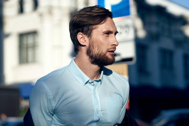 Zakenman in overhemd en jas op straat in de buurt van de close-up van het gebouwportret