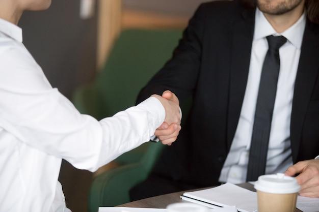 Zakenman in pak handenschudden zakenvrouw respect tonen, close-up bekijken