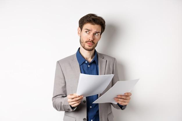 Zakenman in pak kijken door papieren, documenten lezen op het werk en denken, opzij kijken naar logo, bezig op witte achtergrond.