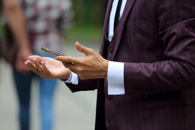 Zakenman in pak met mobiele telefoon in de hand