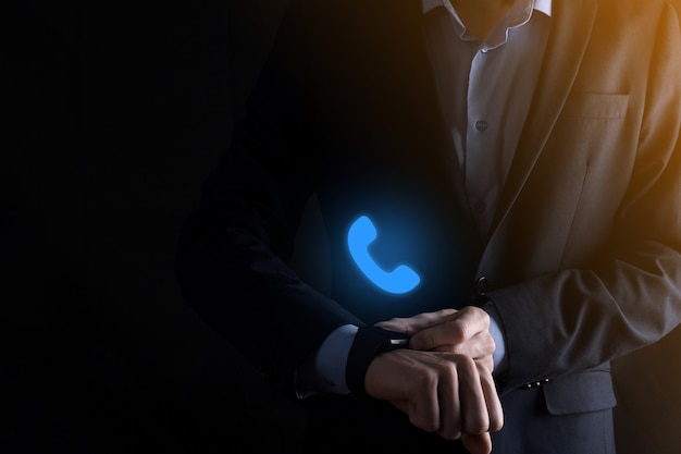 Zakenman in pak op zwarte achtergrond houden telefoonpictogram. bel nu business communication support center