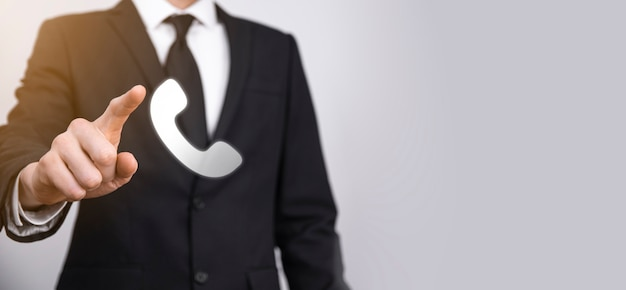 Zakenman in pak op zwarte achtergrond houdt telefoonpictogram. bel nu business communication support center customer service technology concept.