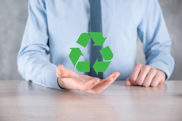 Zakenman in pak over donkere muur heeft een recyclingpictogram, teken in zijn handen. ecologie, milieu en instandhouding concept. neon rood blauw licht.