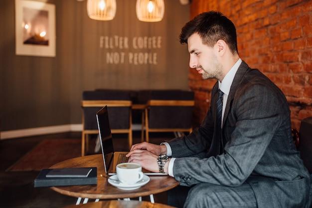 Zakenman in pak zit in het café en kijkt in de laptop